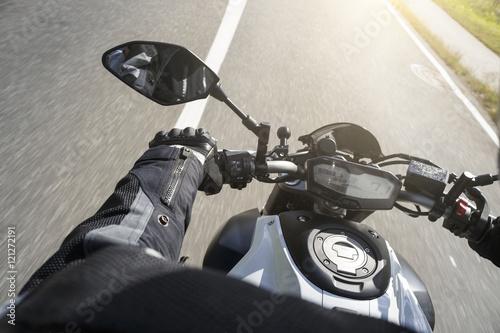 Poster Motorradfahrer fährt auf Straße im Sommer