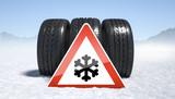 Winterreifen auf Schnee mit Gefahrenzeichen