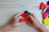 A child plays with colored blocks constructs a model on a light - 121279513