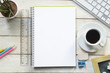An empty page of a notebook in the center of a white wooden table at coffee time. Empty copy space for Editor's text.
