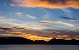 View from the cruise ship sailing in the inside passage of Southwest Alaska as sun sets behind the mountains. - 121288990