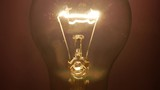 Flashing lamp bulb; light glowing incandescent filament . Detail of incandescent filament of a traditional bulb on the dark