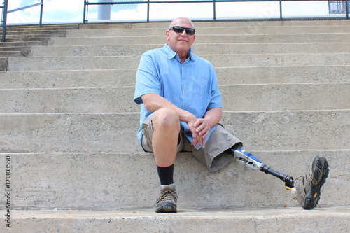 Seated man with prosthetic leg outstretched