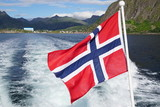 A red and blue Norwegian flag floating over the water from a boat - 121311926