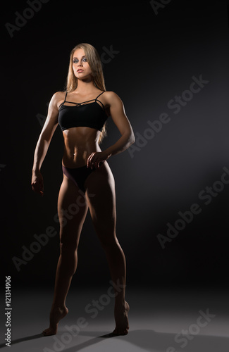 Attractive female bodybuilder posing at camera Poster