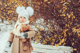 cute baby girl enjoying winter walk in snowy park, wearing warm hat and coat