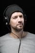 Man with headphones on head at black background
