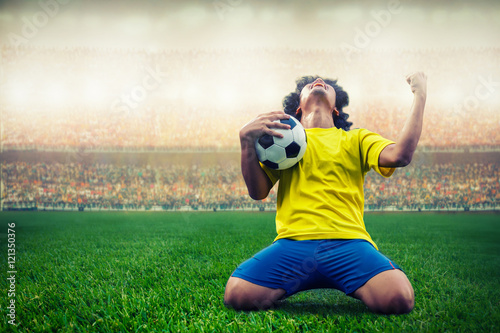 Poster soccer or football player celebrating goal in the stadium during match