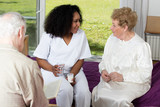 Fototapety Nurse in rehab facility speaking to elder patients