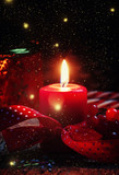 New Year or Christmas composition with red burning candle, ribbo