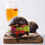 Beef burger with a black bun,with lettuce and mayonnaise and ketchup light beer,served on pieces of brown paper on a rustic wooden table of counter, on a white wooden background.