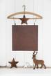 Weihnachtskarte mit einem Blatt Papier alt im vintage Nostalgie Look mit Hirsch und Sternen in weiß und braun als Dekoration.