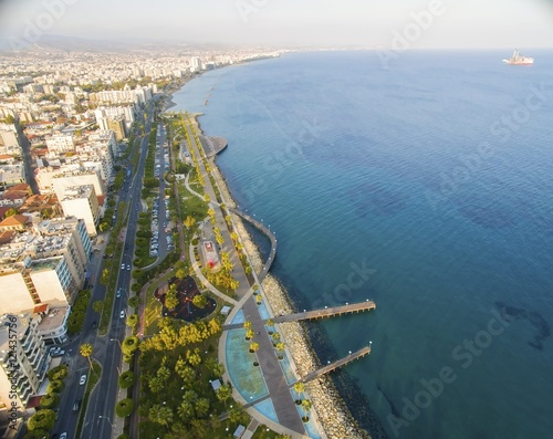 Foto op Plexiglas Cyprus Aerial view of Molos Promenade on the coast of Limassol city in Cyprus. A view of the walk path surrounded by palm trees, pools of water, grass, the Mediterranean sea, piers, rocks and urban skyline.
