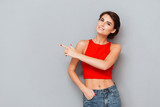 Portrait of a girl in red top pointing finger away