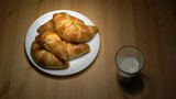 Fresh croissants and milk on wooden table.