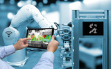 Industry 4.0 concept .Man hand holding tablet with Augmented reality screen software and blue tone of automate wireless Robot arm in smart factory background