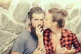 Couple smoking on stony wall background