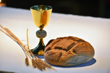 Elegant golden chalice and a loaf of bread on the altar..