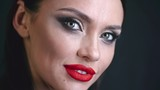 Studio shot of beautiful young woman with red lips turning her face to the camera and smiling