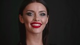 Smiling elegant woman with red lips taking of hands from face to show professional makeup and looking at the camera on the black background