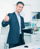 Glad business standing with laptop in hands