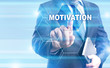 """Businessman is pressing on the virtual screen and selecting """"Motivation""""."""