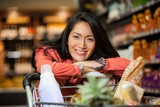 Happy woman leaning on shopping cart