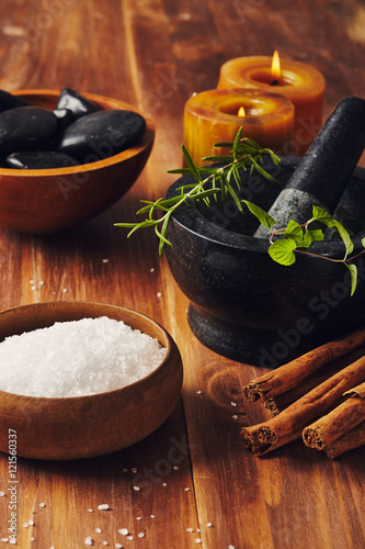 Spa tools, bath salt, mortar with herbs, a bowl with hot stones and candles, some cinnamon sticks on the table © Antonino D'Anna