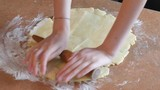 Baker kneading dough with rolling pin on table prepares bread or apple pie