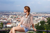 Young woman sit on railing enjoying panorama of Budapest