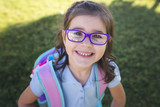 A girl wearing a uniform and a backpack is ready for her first day of school. - 121588781