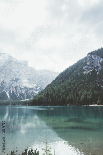 Fototapeta Braies lake with green water and mountains with trees