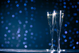 Two glasses of champagne on dark bokeh background - 121609982