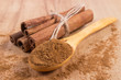 Постер, плакат: Powdery cinnamon and sticks on wooden table seasoning for cooking