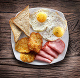 Breakfast - fried eggs with ham and pieces of bread. - 121622941