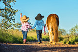 Little cowgirl and cowboy with pony - 121625797