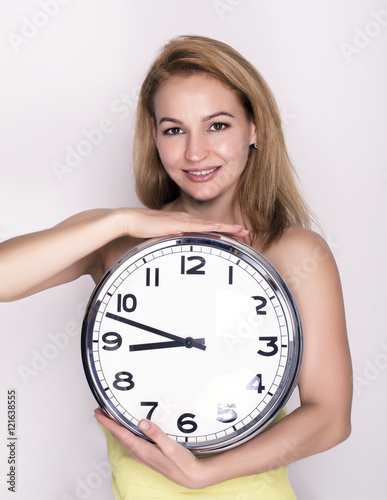 Beautiful young woman looking at a large silver retro clock that she is holding, Poster