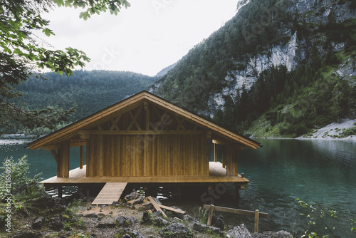 Fototapeta Wood house on lake with mountains and trees