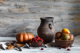 Still life in a rustic style: a set of pottery, pumpkin and pears. Natural light from window.