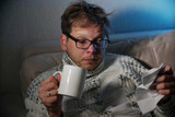 Sick man blowing his nose in the tissue, young ill man in bed  temperature feeling bad infected by winter grippe virus in flu and influenza health care concept