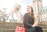 Young woman taking a break in Hamburg. Blonde girl in the city centre, sitting on a staircase, listening music and drinking a coffee. Bicycle and city hall in background.