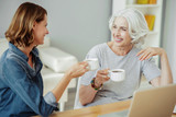 Joyful aged woman and her daughter drinking tea
