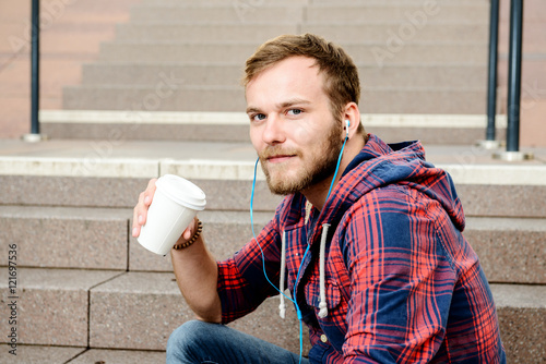 Poster young man in checkered shirt sitting on stairs and drinking coff