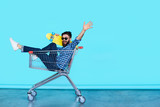Side view of cheerful young man sitting in shopping cart - 121703340