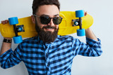 Young stylish confident happy handsome man with skateboard