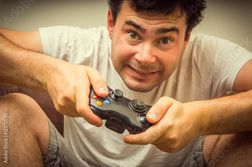 Poster Emotional young addicted man playing video games