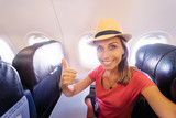 Fototapety Travel and technology. Young woman in plane taking selfie while sitting in airplane seat.