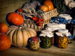 Retro still life with pumpkins and a glass jar with canned food - cucumbers, mushrooms, jam