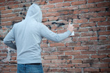 Hooded tagger writing graffiti on urban walls - 121735517