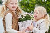 Zwei Mädchen tragen Blumen